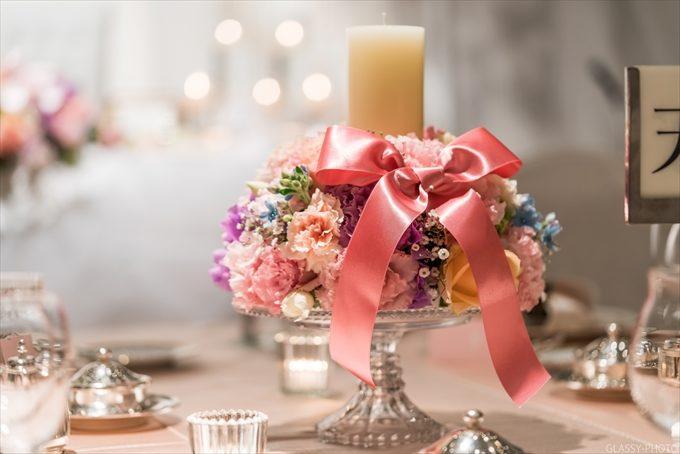 ゲストテーブルにはピンクのリボンの付いたキャンドルがあります