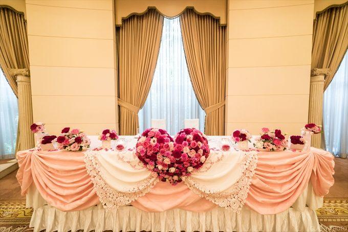 披露宴会場の高砂に飾られた赤やピンクのかわいいお花