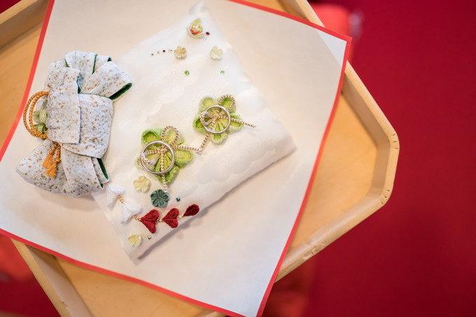 赤じゅうたんに映える手作りリングピローと緑刺繍の上に乗せられた結婚指輪