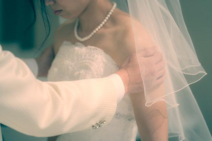 ベールを上げてウェディングキスをする直前に花嫁さんの肩をそっと支える新郎さんの手に優しさを感じます
