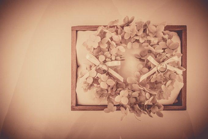 木製の枠に三つ葉のリースとリボンがついたリングピローと結婚指輪