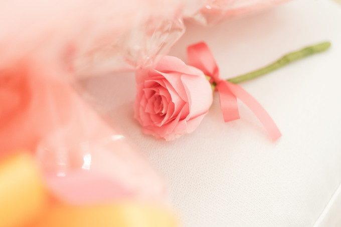 リボンの付いた一輪のバラもオシャレなウェディングアイテムの一つ