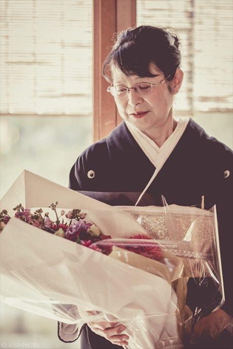 もらった花束を見つめる新郎母