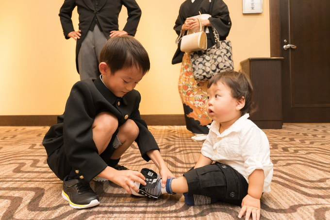 小さい子の靴を履かせる子ども