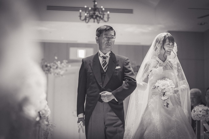 バージンロードを笑顔で歩く花嫁と緊張の父