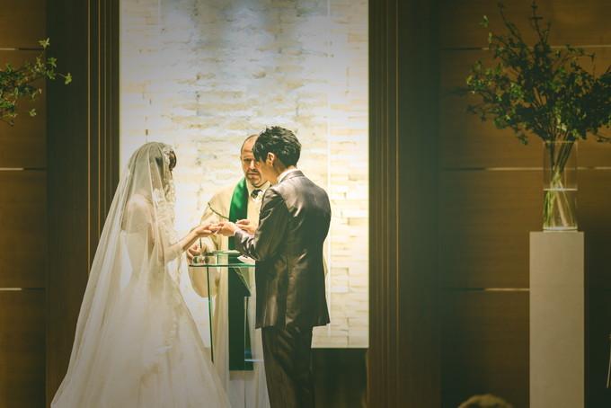 花嫁の指に結婚指輪をはめる新郎