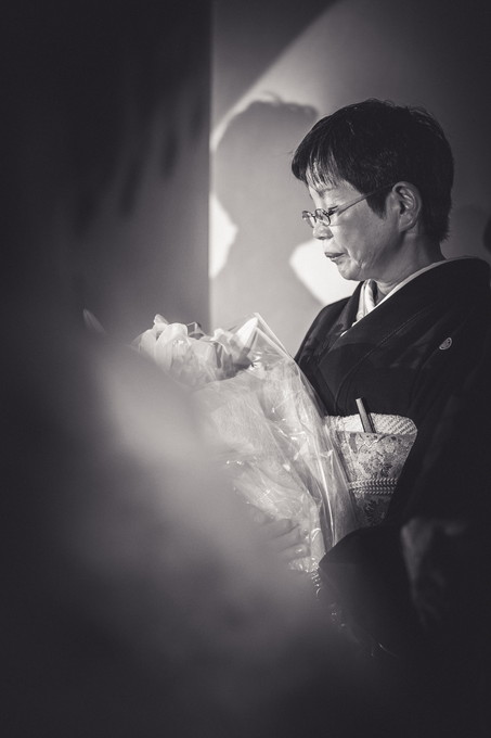 受け取った花束を見つめる母親