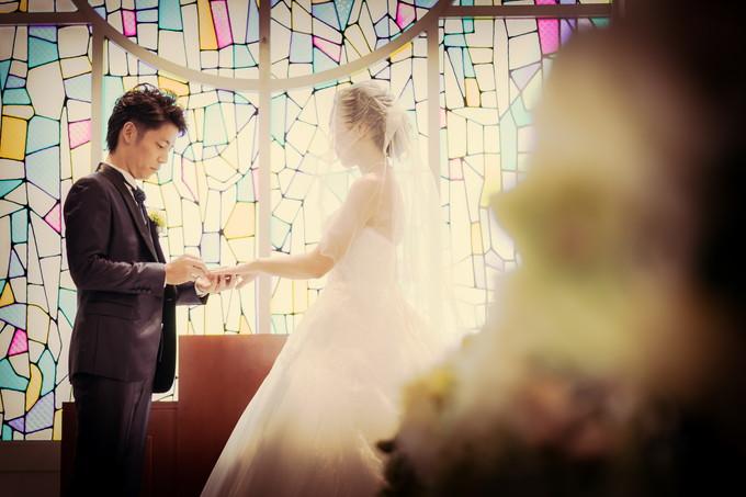 花嫁の手に結婚指輪をはめる新郎