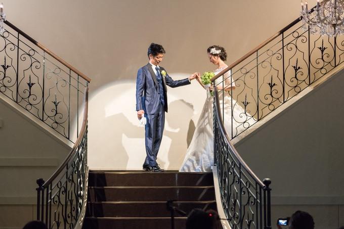 階段で花嫁に手を差し伸べてを迎える新郎
