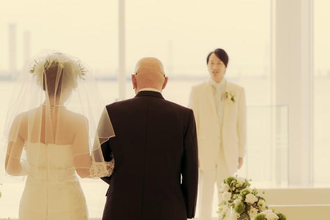 父と腕を組んでバージンロードを歩く花嫁