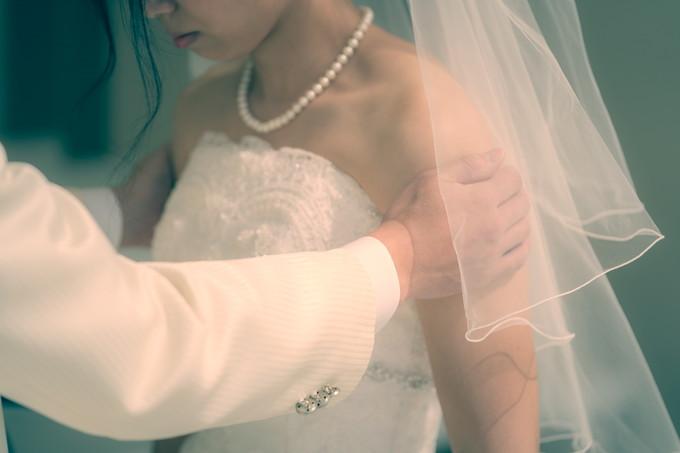 花嫁の二の腕を優しく支える新郎の手