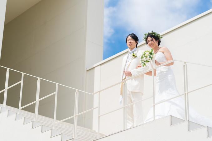 階段の上からゲストを見る新郎新婦