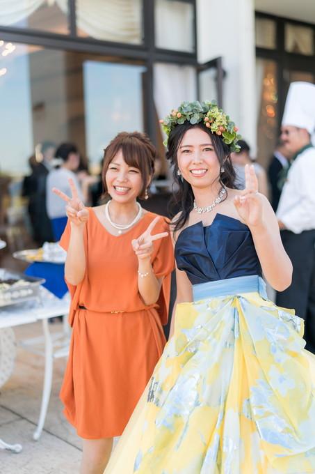 友人とピースをして写真を撮る花嫁