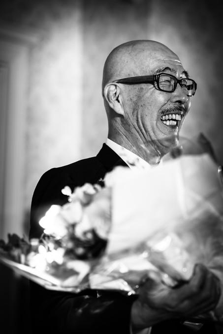 娘から花束を受け取った笑顔の父