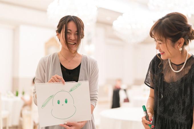 笑顔で絵を披露する女性