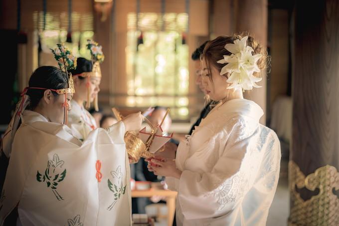 盃のお酒を受ける花嫁