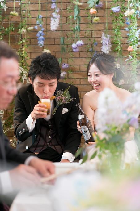 ビールを飲む新郎と笑顔の花嫁