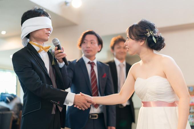 目隠しした新郎と握手する花嫁