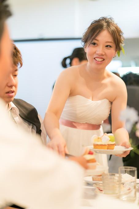 友達にカップケーキをサーブする花嫁