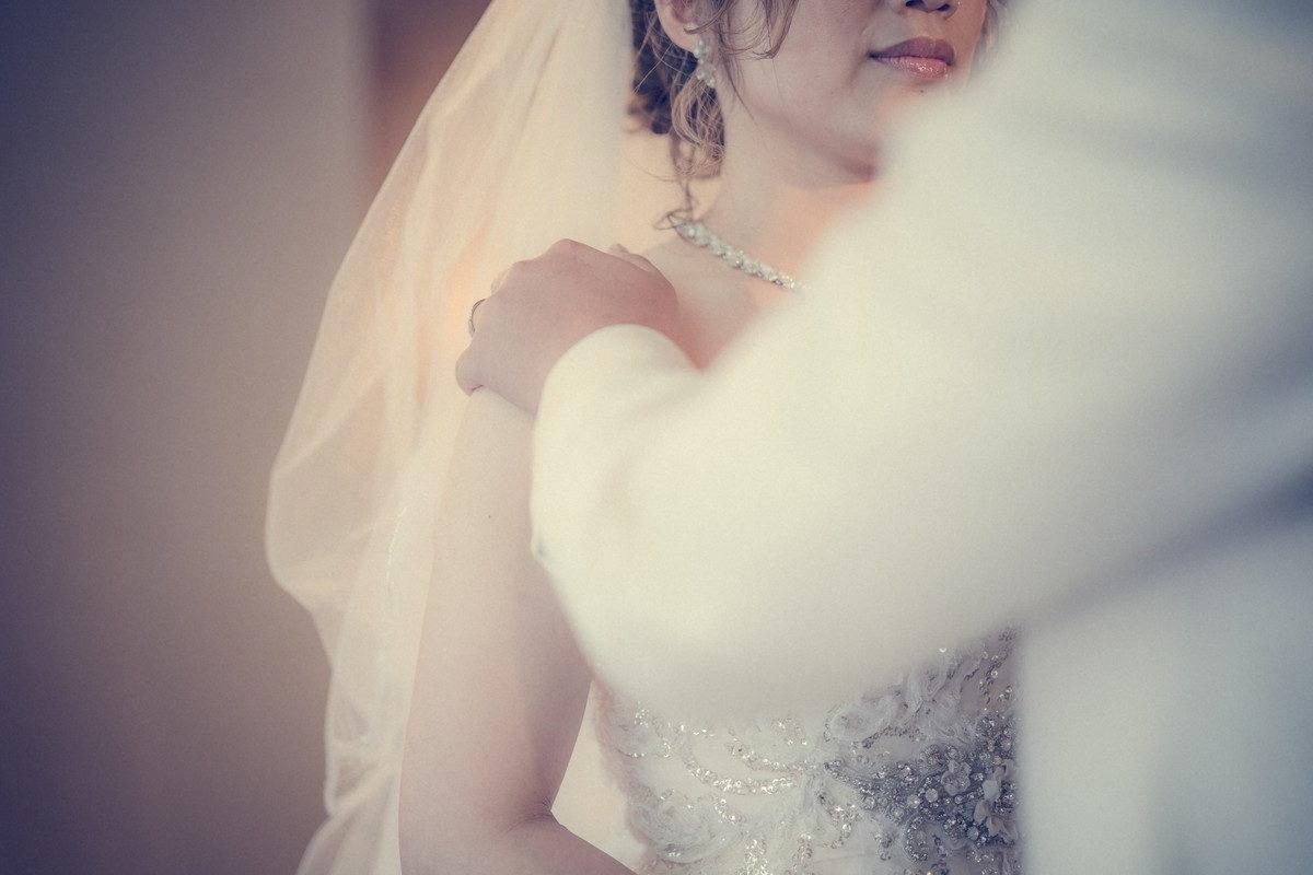 ウェディングキスをするときは花嫁さんの肩から二の腕あたりを優しく支えます