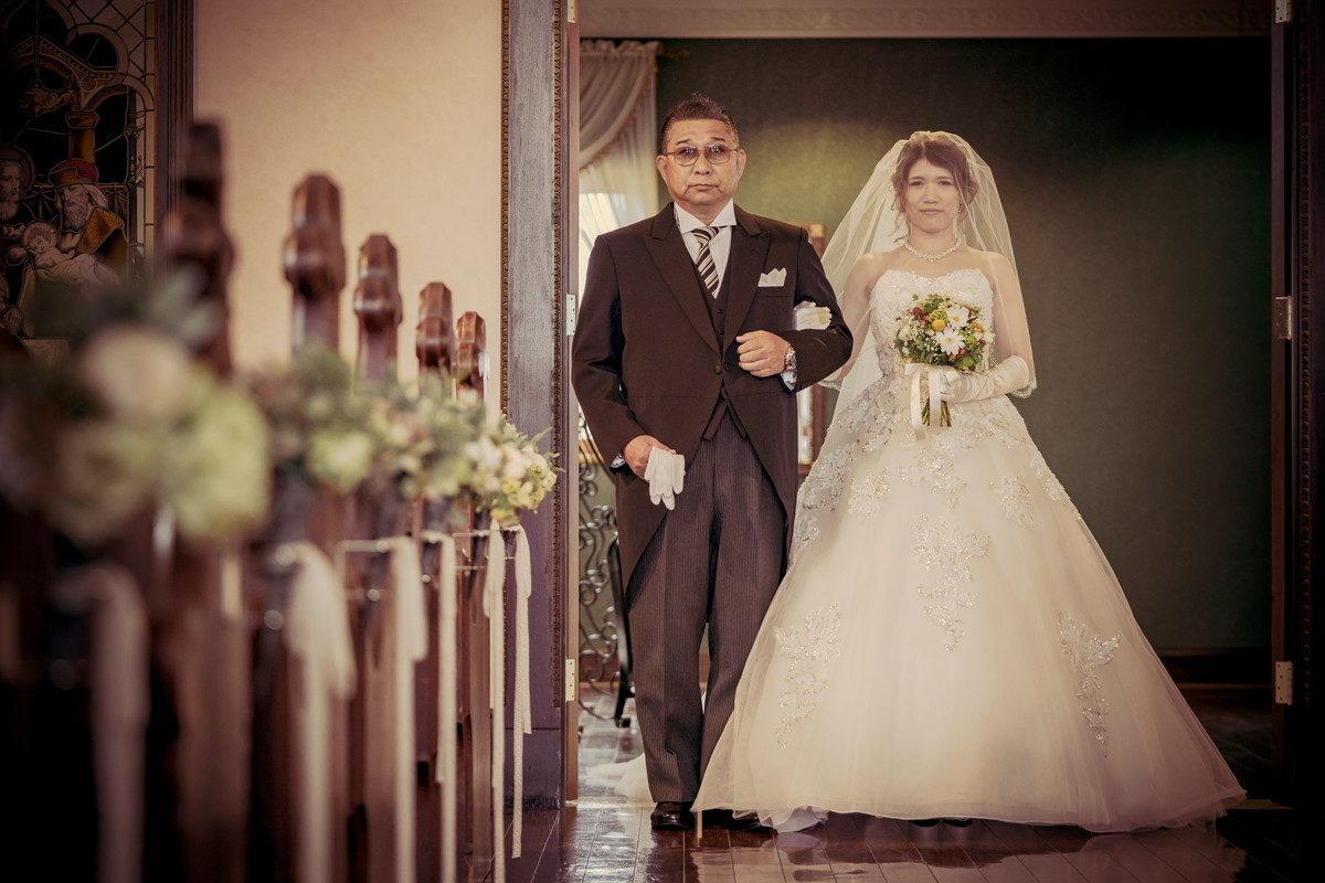 まっすぐに祭壇を見つめてバージンロードを歩くお父さんと花嫁