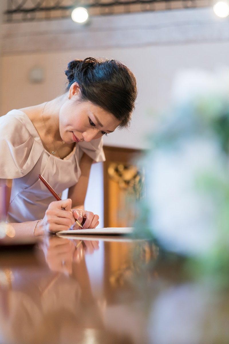 誓約書に立会人署名をする花嫁お姉さん