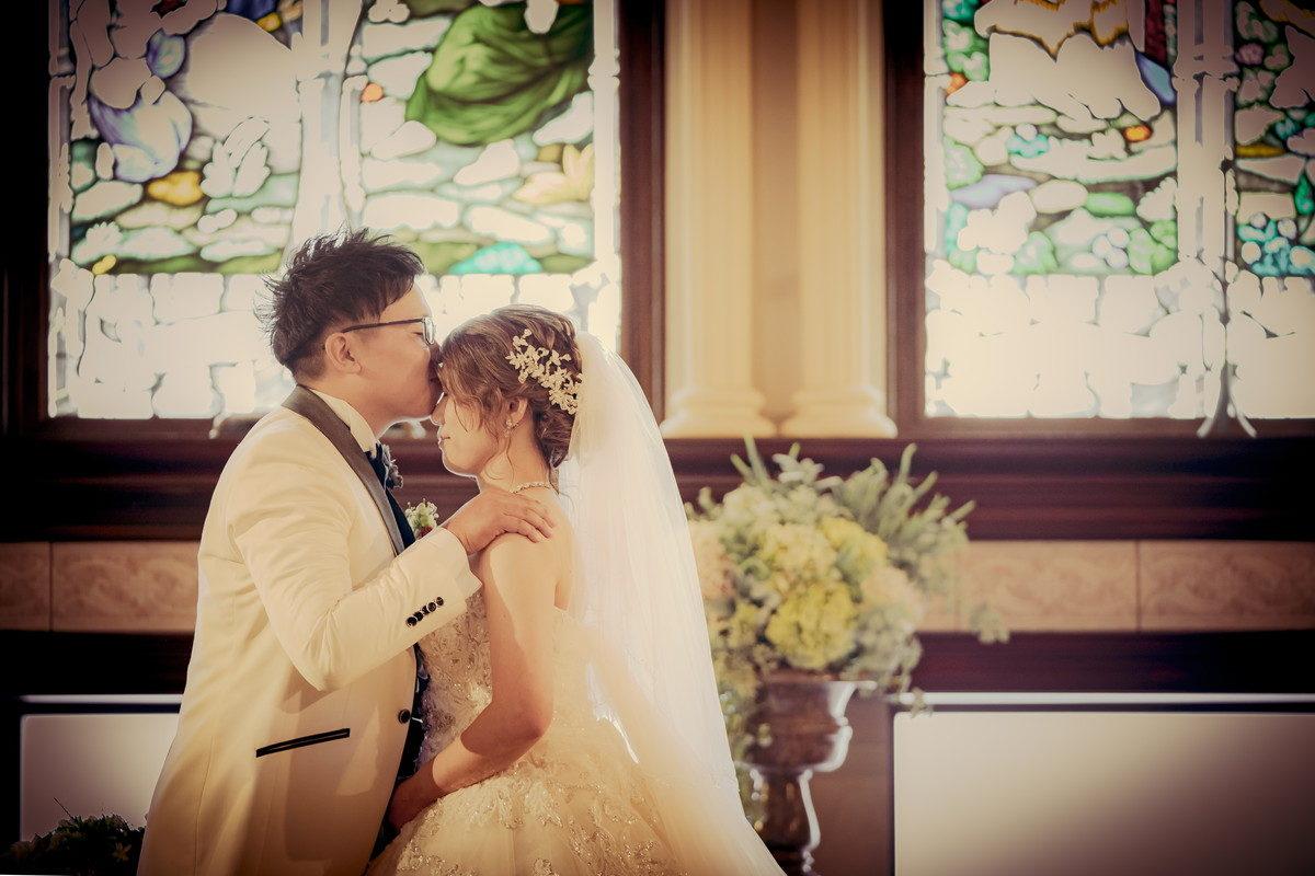 花嫁のおでこに誓いのキスをする新郎