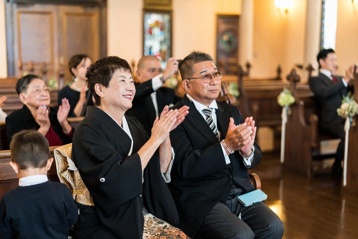 笑顔で祝福の拍手をする花嫁ご両親