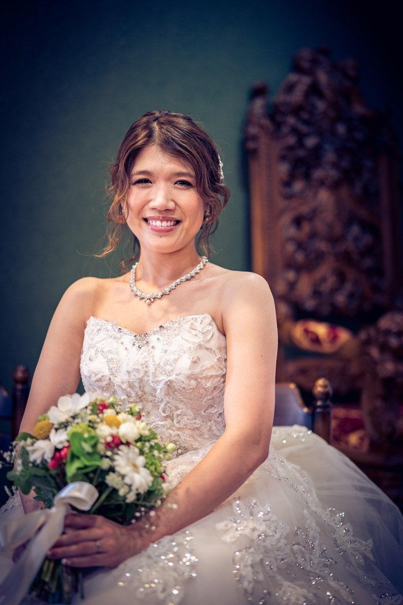 ブーケをもってにっこりとほほ笑む花嫁