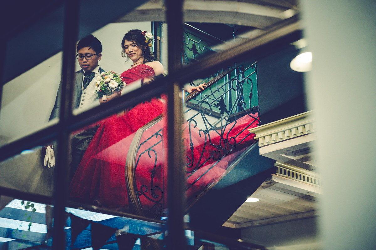 新郎新婦のお二人が階段をおりるシーンを窓越しに