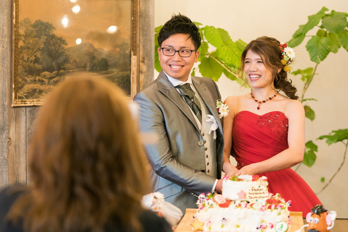ウェディングケーキに入刀して写真撮影に応じる新郎新婦