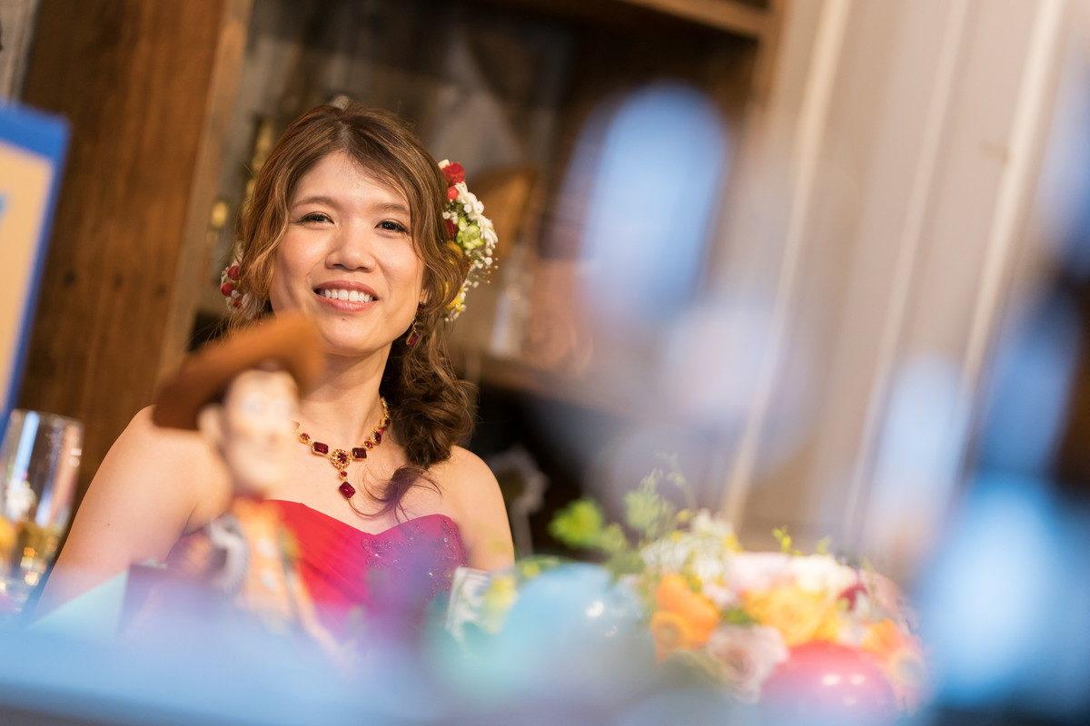 高砂から笑顔でカメラ目線の花嫁