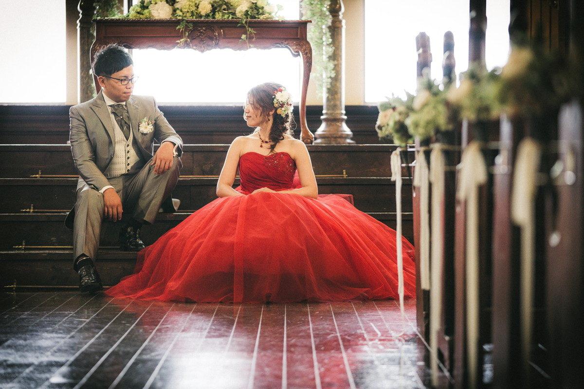 祭壇前階段で座って会話をする新郎新婦