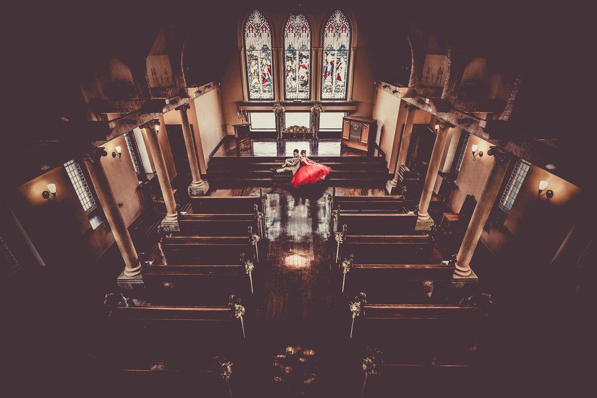 チャペル祭壇前の階段で背中を合わせて座る新郎新婦