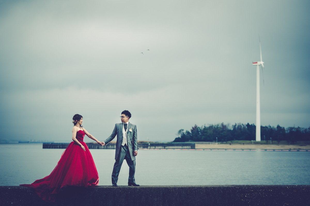 「NEST by THE SEA」さんの前にある海岸堤防で手をつないで歩く新郎新婦
