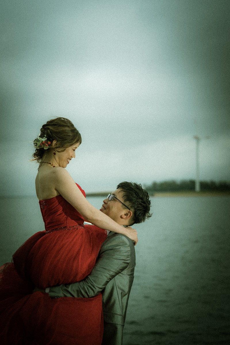 海岸で花嫁を持ち上げるたのもしい新郎