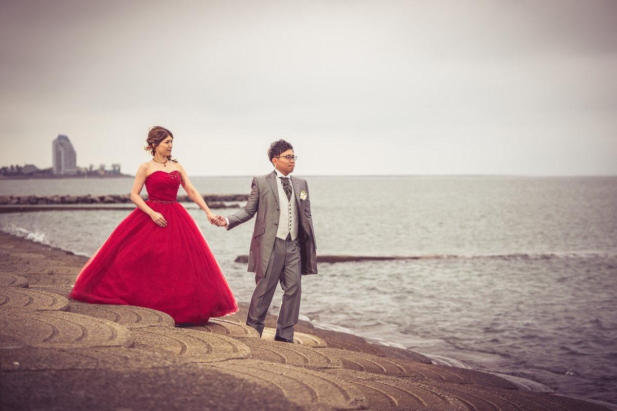 「NEST by THE SEA」さんの前の海岸を手をつないで歩く新郎新婦