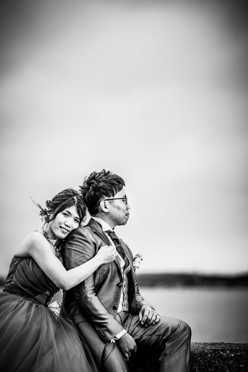 海岸沿いの堤防に座って新郎の背中に寄り添う花嫁