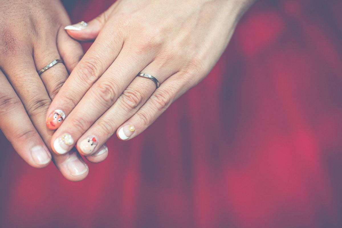 新郎新婦の手にはめられた結婚指輪とトイストーリーなネイルアート