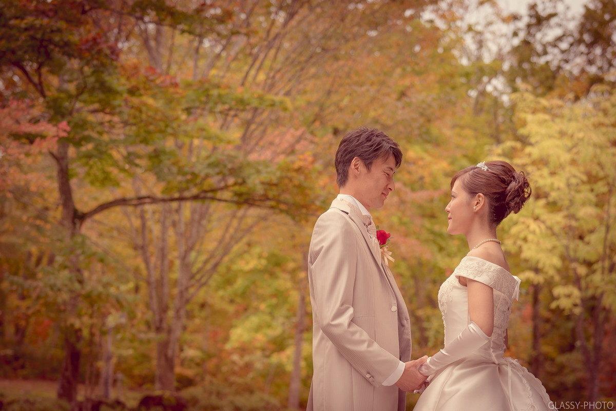 秋の様相をみせる森を背景にセピアな色調で新郎新婦