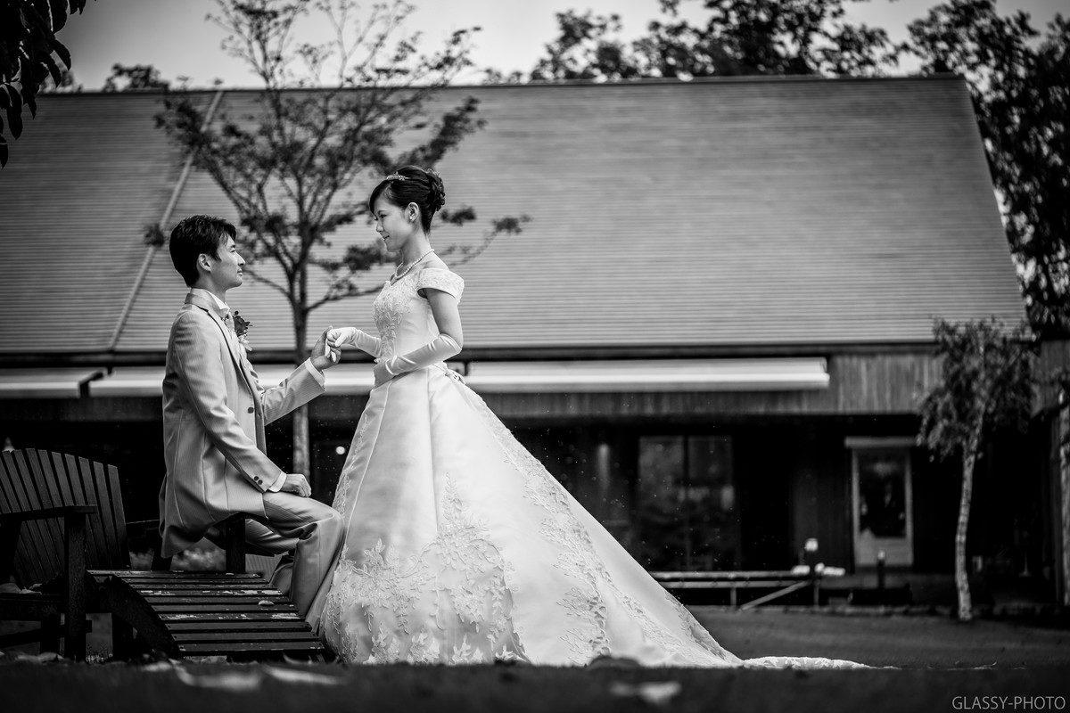 ベンチに座る新郎と手を添える花嫁