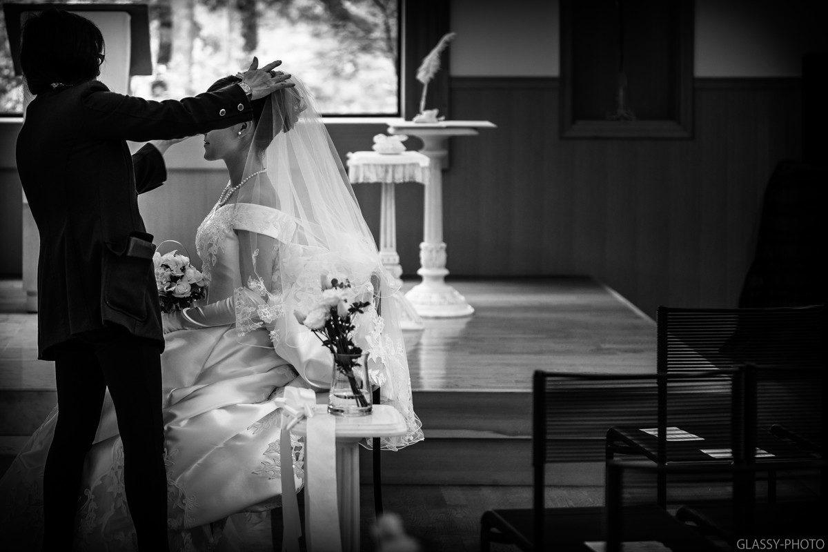 白馬高原教会内にて撮影する前にベールを付けてもらう花嫁