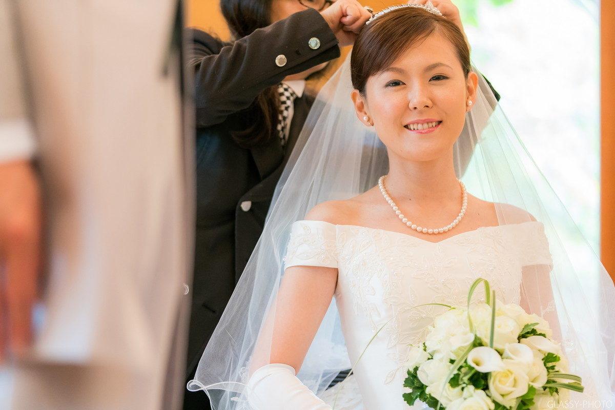ベールを付けてもらってにっこりとほほ笑む花嫁