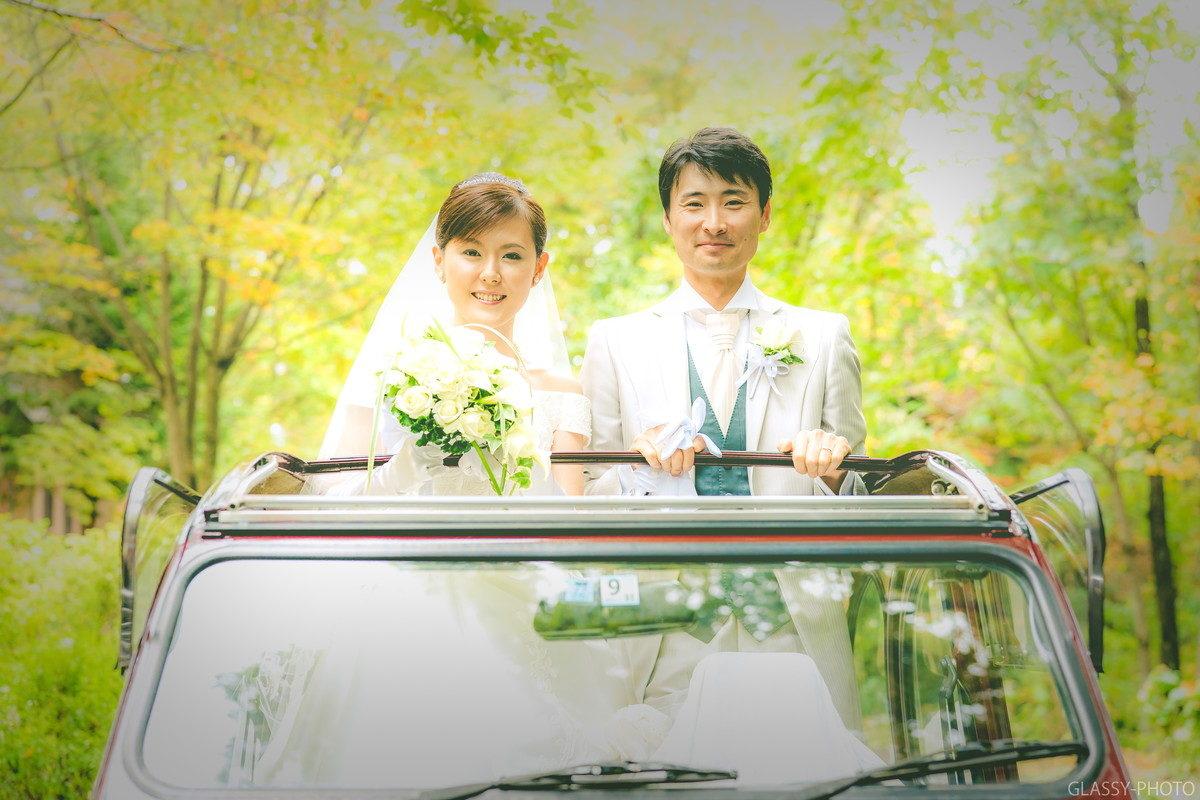 花嫁車に乗って笑顔の新郎新婦