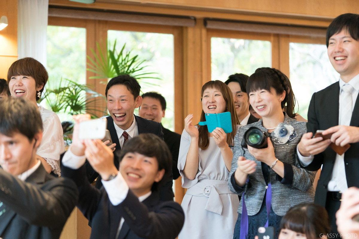 新婦から新郎へのファーストバイトで向こうに写っているゲストのみんなが笑顔になってます