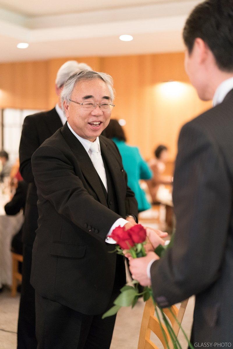 笑顔でバラを渡す新郎のおじさま